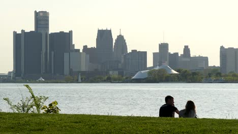 Young-Couple-Sat-in-front-of-Detroit-Cityscape