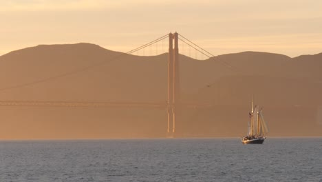 Sailing-Boat-Passing-Golden-Gate-Bridge-at-Sunset