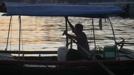 Silhoutted-Man-on-Traditional-Vietnamese-Boat