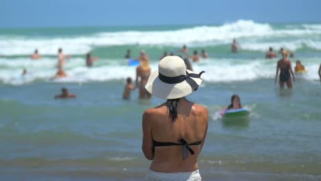 Woman-in-a-Hat-Standing-on-Beach