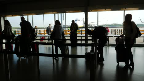 Silhouetted-Passengers-Queuing-in-Airport