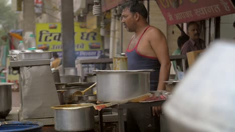 Man-Adds-Spices-to-Food-at-a-Stall