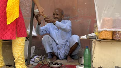 Elderly-Man-Preparing-and-Selling-a-Bag-of-Nuts