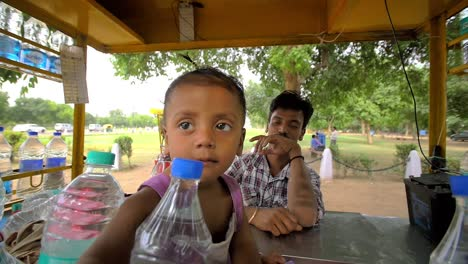 Indian-Toddler-Reaches-Through-Water-Bottles-