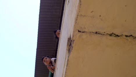 Two-Indian-Boys-Leaning-Over-a-Balcony