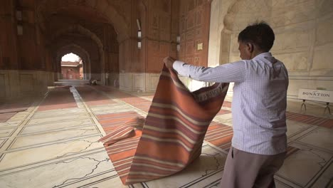 Man-Shaking-Dust-off-of-Prayer-Mats