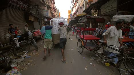 Men-Pushing-Cart-Down-Busy-Street-