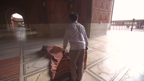 Man-Shaking-Dust-Out-of-Prayer-Mats