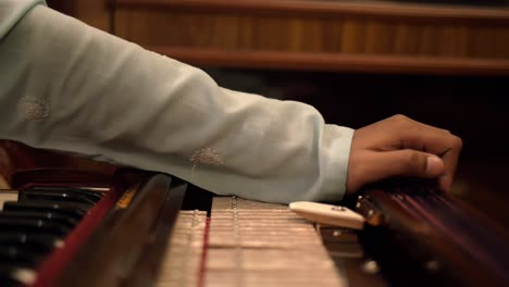Panning-Shot-of-a-Man-Playing-the-Harmonium