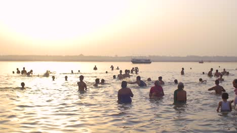 Panning-Shot-of-Bathers-in-the-Ganges-at-Sunset