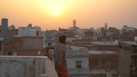 Man-Climbing-Onto-Rooftop-at-Sunset