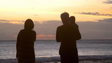 Silhouetted-Family-Walking-Along-Beach-at-Sunset