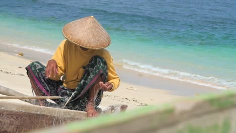 Fisherman-Untangling-Net-on-Beach