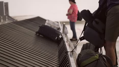 Man-Collecting-Rucksack-from-Baggage-Claim