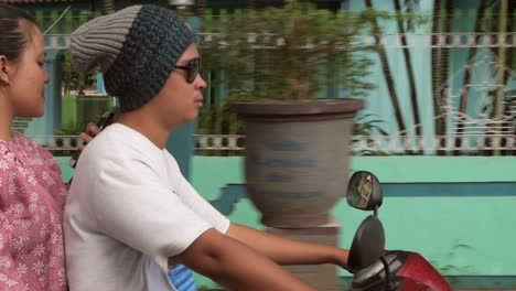 Couple-Riding-Motorbike-Through-Indonesian-Village