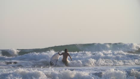 Surfer-Walking-Through-Large-Waves