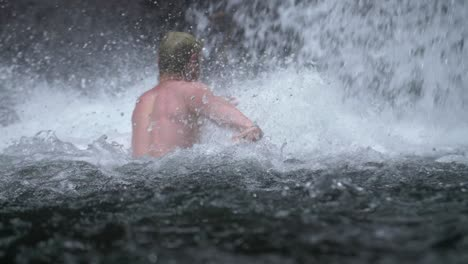 Man-Swimming-Under-a-Waterfall
