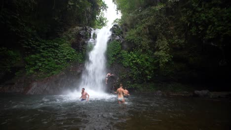 Reveal-Shot-of-Swimmers-Under-a-Waterfall