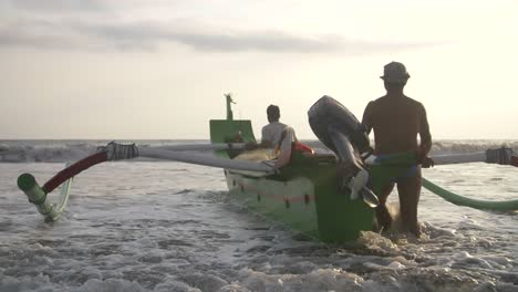 Men-Pushing-Indonesian-Outrigger-into-Ocean