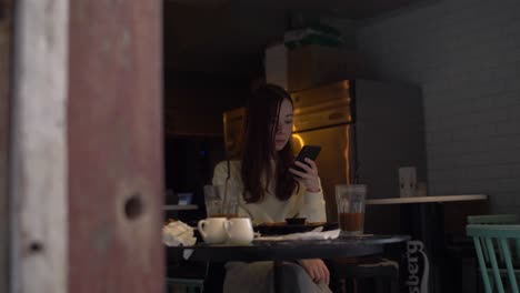 Young-Woman-oh-Her-Phone-in-a-Cafe