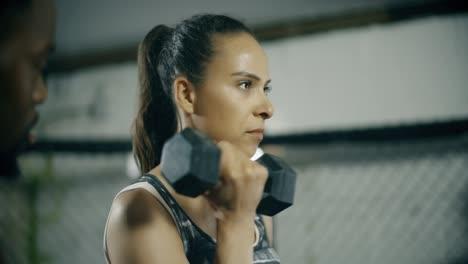 Mujer-que-trabaja-con-entrenador-personal-en-el-gimnasio