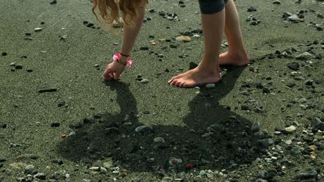 Girl-Picks-Up-Pebble---Beach