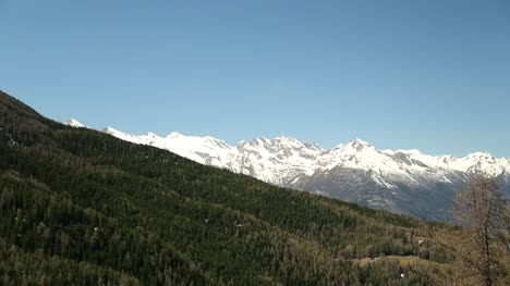 Tree-Lined-Hills-With-Snow-Capped-Mountains
