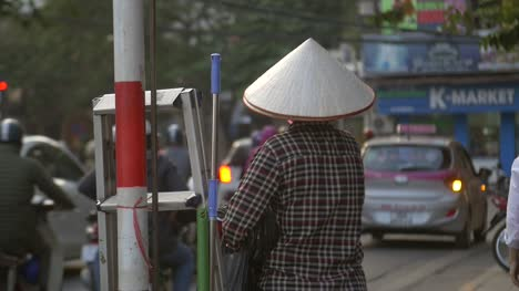 Vietnamese-Lady-Wearing-a-Conical-Hat-stood-on-a-Busy-Street