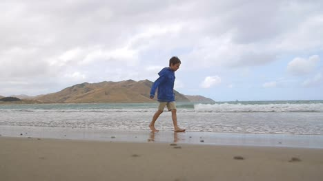 Young-Boy-Walking-Along-Windy-Beach
