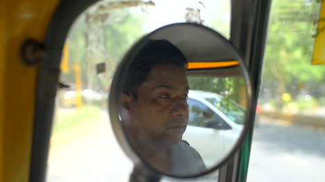 Handheld-Shot-of-a-Tuk-Tuk-Driver-in-Wing-Mirror