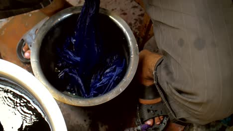 Man-Dyeing-Clothes-Next-to-Pots-of-Pigment