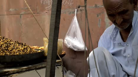 Elderly-Man-Fills-and-Weighs-a-Bag-of-Chickpeas