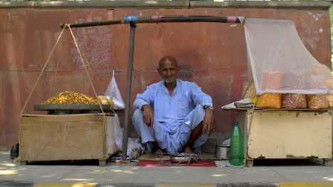 Elderly-Man-Sitting-at-Food-Stall-on-Indian-Street