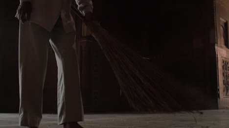 Man-Sweeping-Dusty-Floor