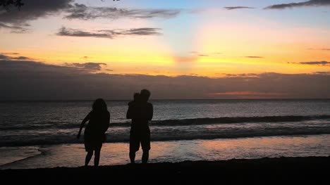 Silhouetted-Family-On-Beach-at-Sunset