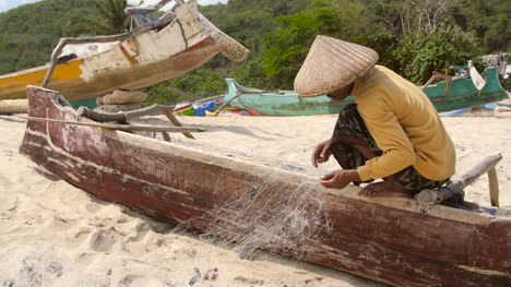 Fisherman-Untangling-Nets-on-a-Beach