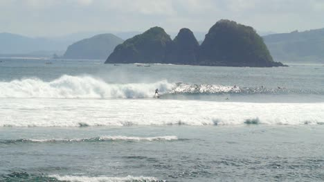 Surfer-Surfing-Past-a-Small-Island