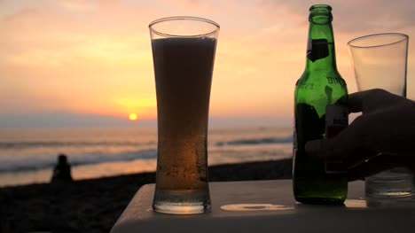 Pouring-Beer-in-a-Glass-on-a-Beach-at-Sunset