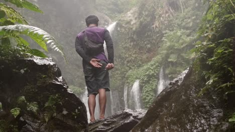Low-Level-Shot-of-a-Man-Sanding-by-a-Waterfall