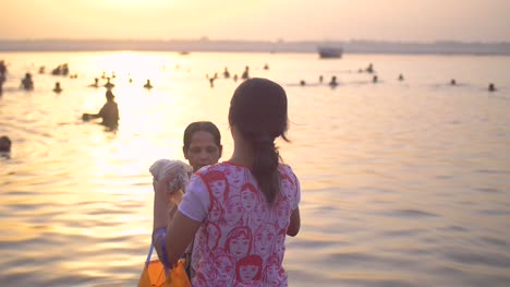 Girl-Handing-Towel-to-Woman-in-the-Ganges