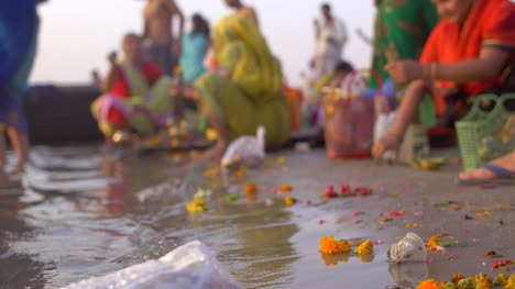 Low-Level-Shot-of-Bags-of-Flowers-by-the-Ganges