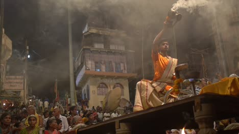 Man-Waves-Incense-and-Rings-Bell-before-a-Crowd