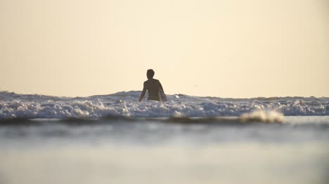 Low-Shot-of-a-Surfer-Walking-in-the-Sea