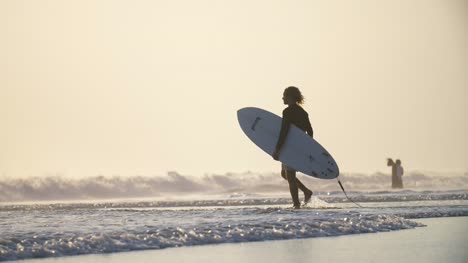 Man-Walking-into-the-Sea-with-a-Surfboard