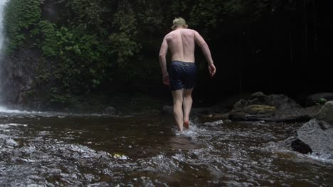 Man-Walking-Through-a-Woodland-Stream