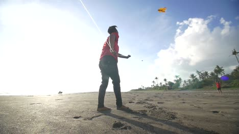 Man-Pulling-on-a-Kite-String-on-a-Beach