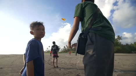 Young-Boy-Watching-Kite-Flyers-on-a-Beach