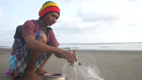 Man-Untangling-a-Fishing-Net-on-a-Beach