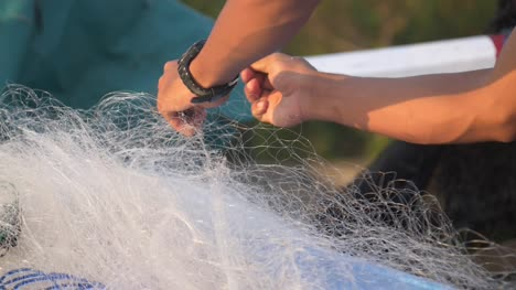 Hands-Removing-Stick-from-Fishing-Net