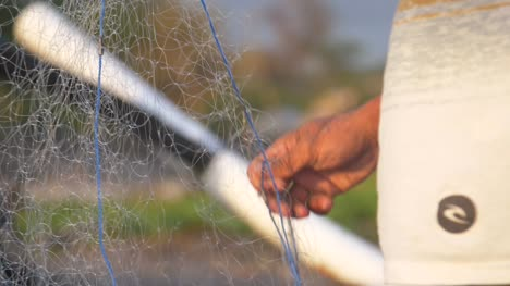 Hands-Shaking-Out-a-Fishing-Net